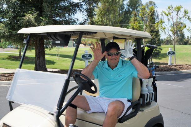 Man has bith hands raised by his face smiling in a Golf Kart -RTL Pro-Life Fundraiser