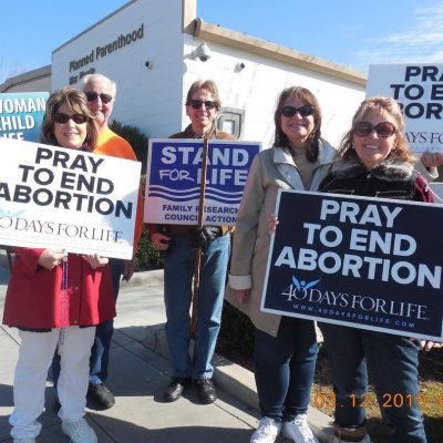 Pro life group holding pro life signs smiling